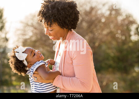 African American mother holding her daughter smiling. - Stock Image