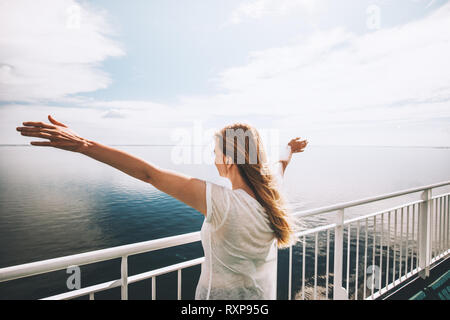 Woman tourist sea traveling by ferry happy raised hands active lifestyle adventure weekend trip vacations outdoor - Stock Image