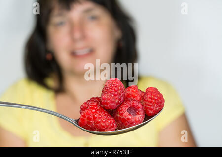 Red juicy raspberries on spoon. Blurred woman in background. Detail of stainless steel spoonful of fresh ripe raspberry fruits and blurry female face. - Stock Image