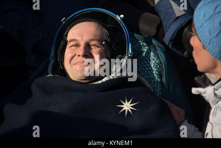 Roscosmos cosmonaut Sergey Ryazanskiy rests in a chair shortly after he and NASA astronaut Randy Bresnik, and ESA - Stock Image