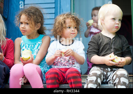 Children sitting on steps and eating apples - Stock Image