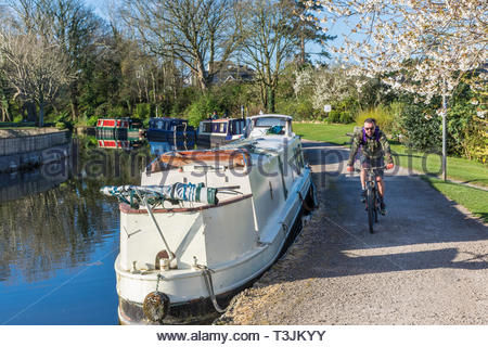 Hest Bank, Lancashire, UK, 10 April 2019. UK Weather: Clear blue sky and bright sunshine after an overnight frost as a cyclist makes his way along the towpath by the Lancaster Canal. Further sunshine is forecast for the rest of the day, but with an Easterly breeze it will feel cool out of the sunshine. Credit Keith Douglas News/Alamy Live News - Stock Image