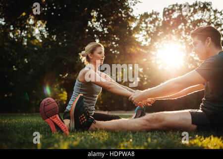 Healthy young man and woman exercising in the park. Smiling caucasian couple holding hands and stretching in morning. - Stock Image