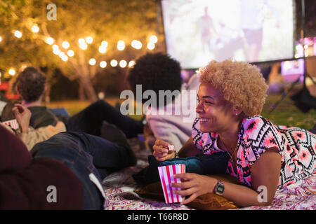Happy woman eating popcorn, watching movie with friends in backyard - Stock Image
