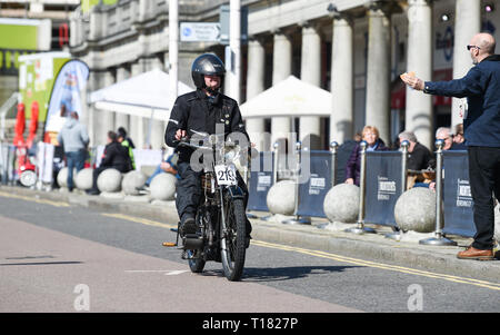 Brighton, UK. 24th March 2019. Kevin Hellowell on his 2012 New Hudson is offered a roll as he nears the finish of the 80th Anniversary Pioneer Run for pre 2015 veteran motorcycles in Brighton . The run organised by the Sunbeam Motor Cycle Club begins on the Epsom Downs in Surrey and finishes on Madeira Drive on Brighton seafront Credit: Simon Dack/Alamy Live News - Stock Image