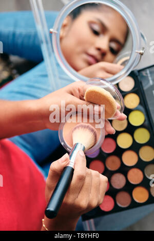Mirror Close-Up Of Young Woman Applying Make-Up For Beauty - Stock Image