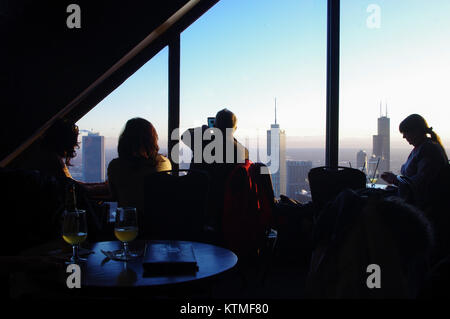 Tourists take in the Chicago Skyline from the John Hancock Tower Observation deck. A man uses his phone to take - Stock Image