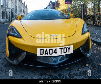 A yellow 2017 McLaren 570S Coupe sports car, parked in a sidestreet - Stock Image