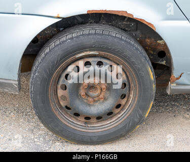 A rusty neglected wheel and fender on an automobile. - Stock Image