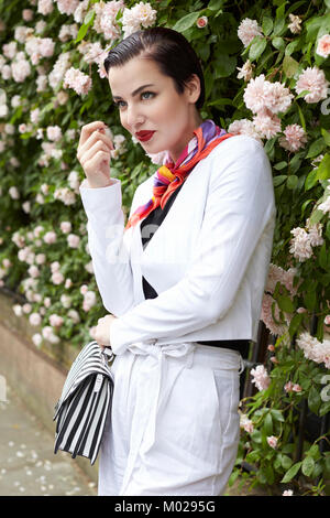 Woman in white linen suit standing by flower bush, side view - Stock Image