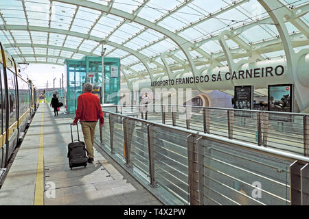 Man with luggage in covered walkway leading to Metro and railway transport links at Aeroporto Francisco sa Carneiro in Porto Portugal EU  KATHY DEWITT - Stock Image