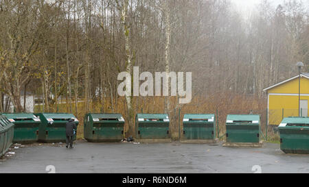 FLODA, SWEDEN - NOVEMBER 21 2018: Female person walking up to recycling container at public outdoor recycling centre - Stock Image