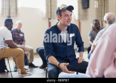 Young man talking in group therapy in community center - Stock Image