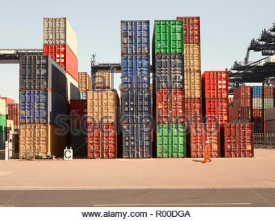 Dock worker by stack of cargo containers - Stock Image