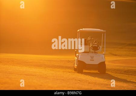 Golf buggy in sunrise - Stock Image