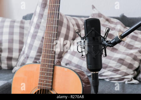 Condenser microphone on a stand with acoustic guitar in the background - Stock Image