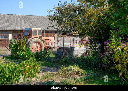 old tractor standing in a rural village house garden zala county hungary - Stock Image
