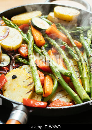 Mixed vegetables (asparagus, zucchini, bell pepper, carrots, onions, potatoes) being grilled in a cast iron grill pan. - Stock Image