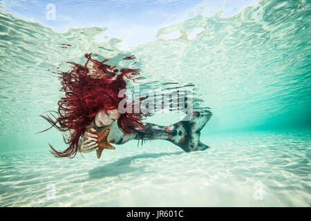Redhead mermaid and her sea star companion, Nassau - Stock Image