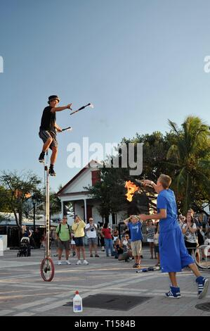 Male street performer pedaling on a unicycle while juggling, entertaining crowds, at Mallory Square on Key West, Florida Keys, Florida, USA - Stock Image