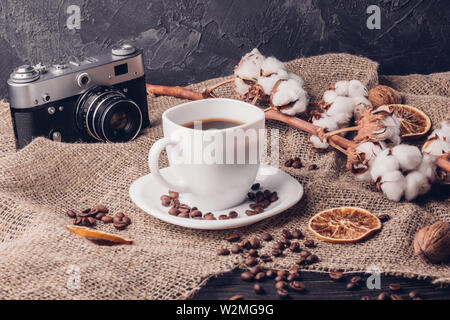 Cup of coffee and coffee beans on a wooden table next to a retro camera and cotton on a branch - Stock Image