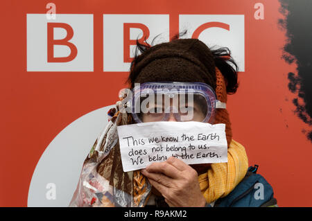 London, UK. 21st December 2018. A woman holds up a quotation from a native American 'This we known the Earth does not belong to us. We belong to the Earth'. Climate campaigners from Extinction Rebellion protest at the BBC calling it to stop ignoring the climate emergency & mass extinctions taking place and promoting destructive high-carbon living through programmes such as Top Gear and those on fashion, travel, makeovers etc. The protest, organised by the Climate Media Coalition (CMC) and its director Donnachadh McCarthy brought mannequins wrapped in white cloth to the BBC representing the bod - Stock Image