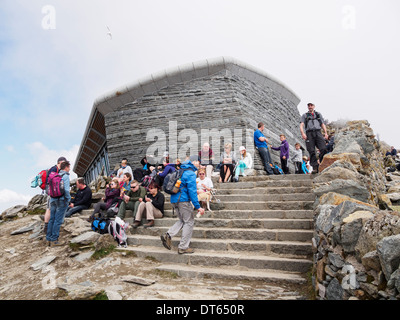 People sitting outside Mount Snowdon summit café Hafod Eryri on a busy summer weekend in Snowdonia National Park North Wales UK - Stock Image