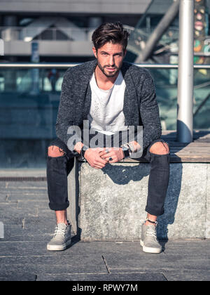 One handsome man in city environment, sitting - Stock Image