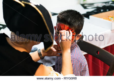 Poznan, Poland - March 3, 2019: Woman in pirate costume painting face of a boy during a birthday celebration party. - Stock Image