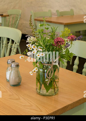 Simple, small, flower arrangement in glass jam jar used as table decoration in cafe - Stock Image