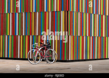 Bicycles at Coloured Pattern in Wooden Cladding at Clarence Dock Leeds West Yorkshire England - Stock Image