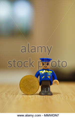 Playtive toy mailman figure standing next to a 50 eurocent coin - Stock Image