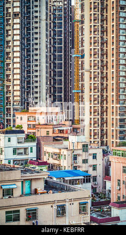 A 40 storey wall of new apartments are under construction next to an existing slightly more eclectic and lower level - Stock Image