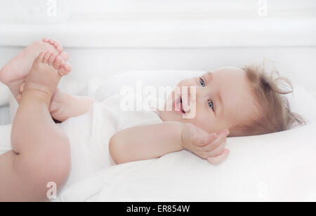 cute little happy baby boy lying on soft white pillow, happy family concept - Stock Image