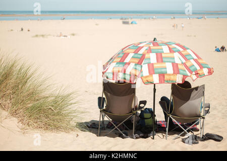 A couple relax under a beach umbrella on a white sand beach in Norfolk, UK - Stock Image