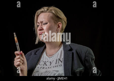 Woman looking at electronic cigarette and is doubting - Stock Image