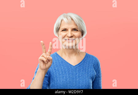 portrait of smiling senior woman showing peace - Stock Image