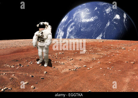 An astronaut surveys his situation after being marooned on a barren planet. A large, water covered world rises above - Stock Image
