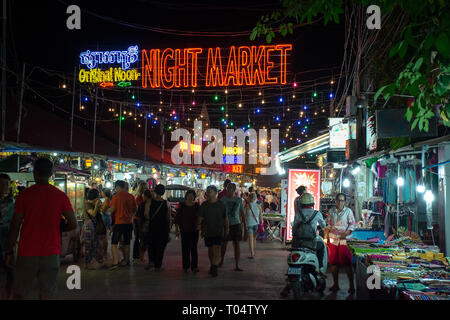 Busy night on the popular tourist Night Market street, with neon sign, Siem Reap, Cambodia. - Stock Image
