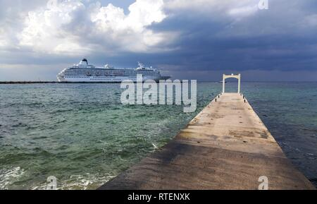 Large Cruise Ship Liner and Stone Pier against the background of dramatic stormy sky in port of Cozumel, Mexico - Stock Image