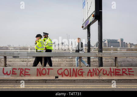 Met police officers walk across the closed Waterloo Bridge on day 4 of protests by climate change environmental activists with pressure group Extinction Rebellion, on18th April 2019, in London, England. The Met have been criticised for allowing the protests to continue their occupations of major roads and junctions such as Waterloo Bridge and Oxford Circus. - Stock Image