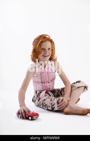 Young girl with red hair and freckles, age 7, playing with a toy car. Model released. Studio shot.       Ref: CRB538_103609_0038  COMPULSORY CREDIT: M - Stock Image