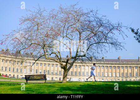 Bath, UK, 29th March, 2019. A man enjoying the warm sunshine is pictured running in front of the Royal Crescent. Credit:  Lynchpics/Alamy Live News - Stock Image