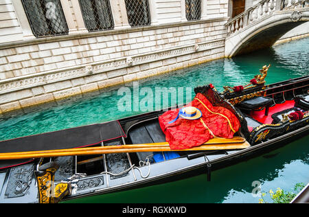 A fish swims under Venetian gondola with oars, gondolier hat, striped shirt and red blanket as it sits unoccupied in a colorful canal in Venice Italy - Stock Image