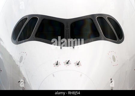 Close front outside view of a white big jet plane cockpit. - Stock Image