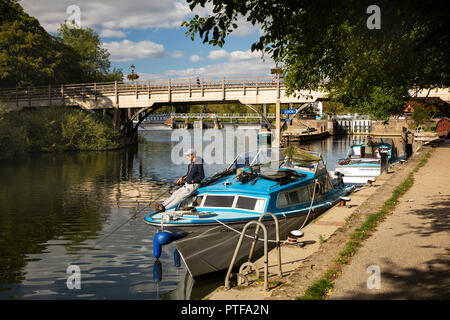 England, Berkshire, Goring on Thames, angler fishing from boat moored on River Thames by locks and bridge to Streatley - Stock Image