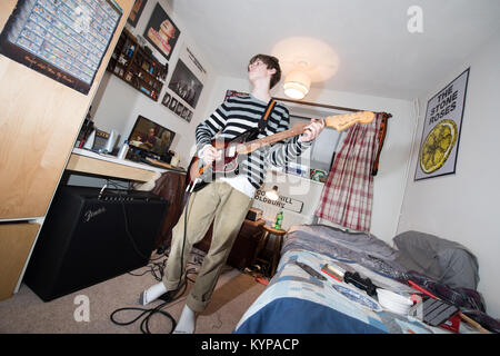 Moody white teenage boy in a stripey jumper plays a Fender Jaguar guitar in a small bedroom surrounded by band posters - Stock Image