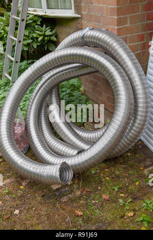 Roll of chimney liner waiting to be installed for a wood burning stove - Stock Image