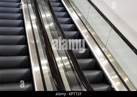 Metal escalator staircases with nobody riding the steps - Stock Image