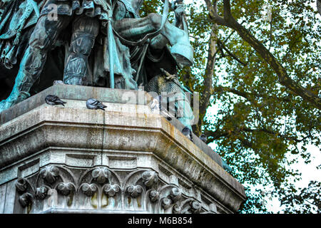 One white pigeon and several other dark pigeons perch on the statue of Charlemagne with his horse in the square - Stock Image